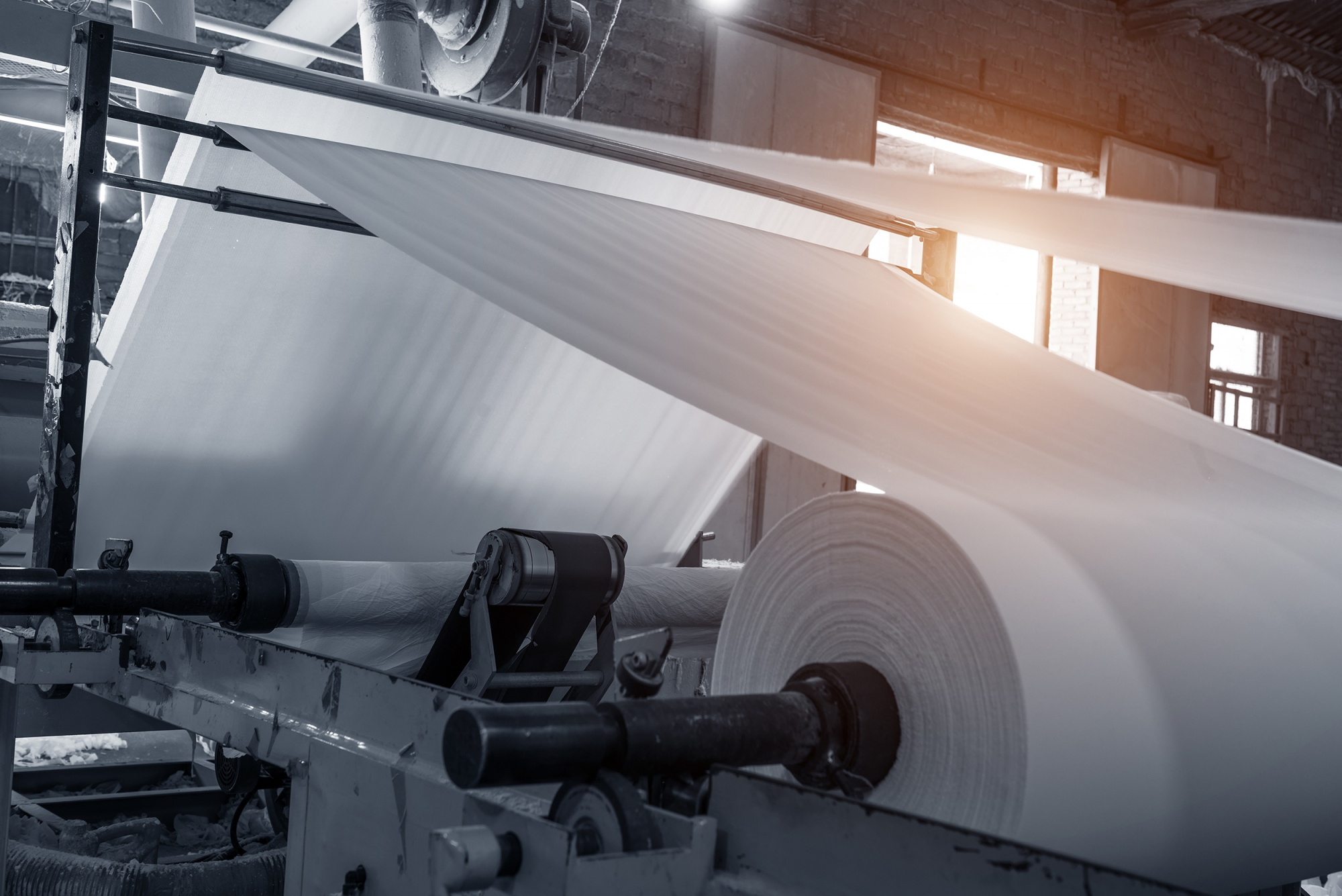 A piece of paper rolling equipment rolling up a spool of white paper
