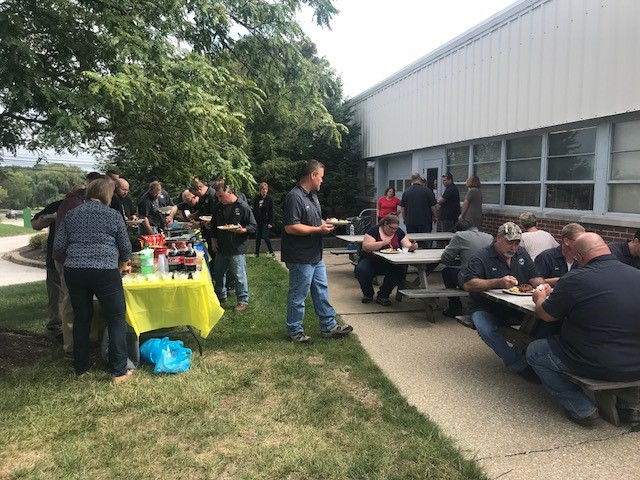 A group of Solon employees outside having a picnic at a set of tables