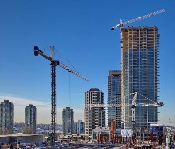 Multiple large cranes surrounding a skyscraper being constructed
